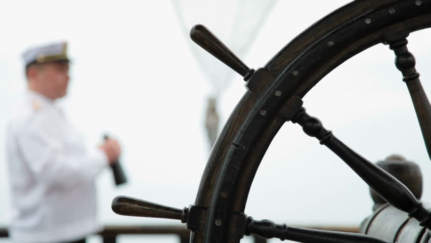 wooden ship wheel in the foreground, a sailor looking through bioculars in the background. - HD stock footage clip