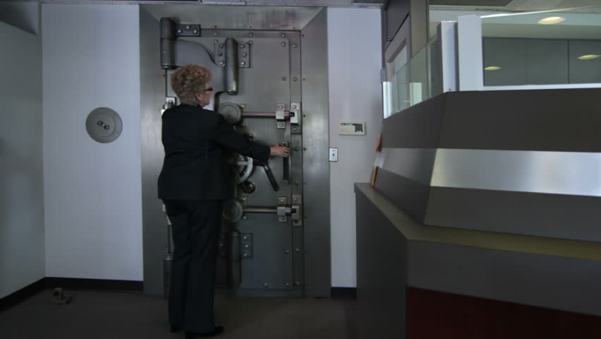 Woman opens a large bank vault door revealing the safe deposit boxes inside.