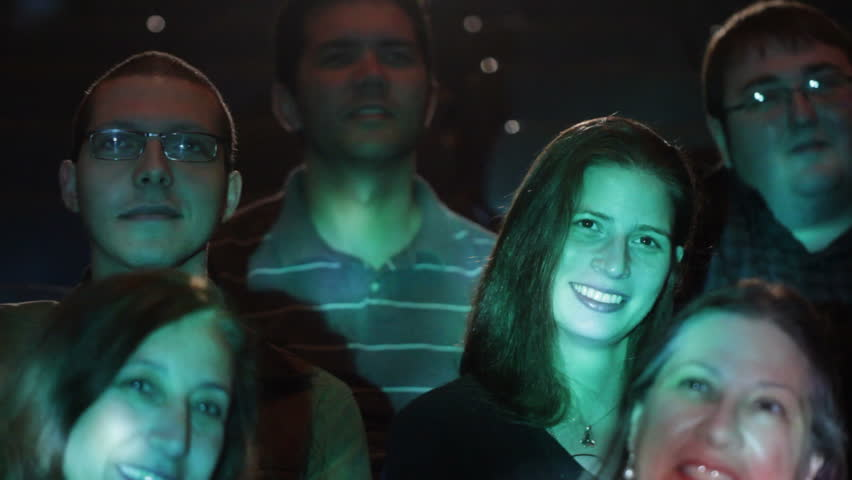 Various adults watching a movie with emphasis on one young couple. Jib movement and projections on audience faces.