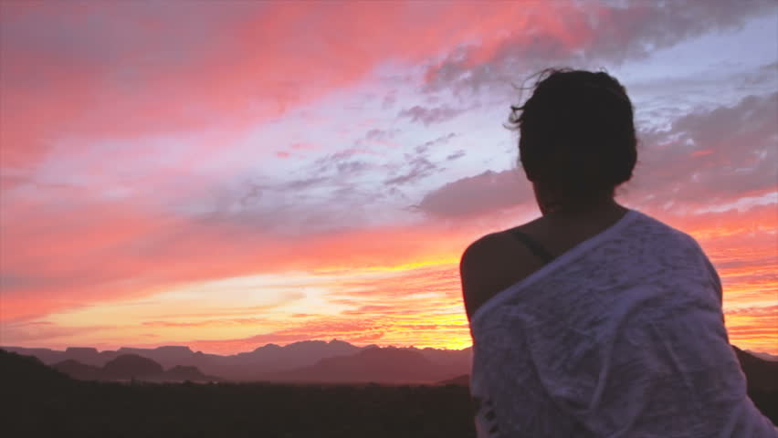 Woman in a gazebo watching sunset falling over the oasis in Baja California, Mexico - HD stock footage clip