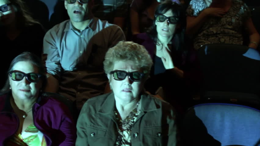 Audience jumps back at a dramatic event during a 3D movie screening. Camera