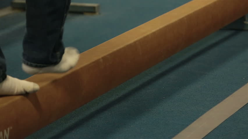 Man walking balance beam gym. Gymnasium athletic equipment with various different strength and agility building stations. Balance and body building preparation for competition and personal training. - HD stock video clip