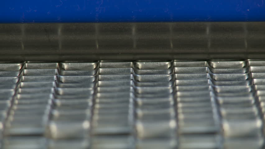 Close up on an industrial conveyor belt with a steel roller visible. Loopable
