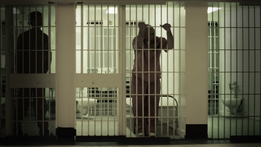 Inmate standing at the bars of his prison cell. Neighboring inmate can be seen
