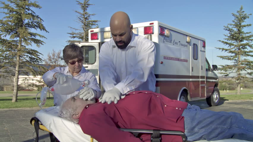Two paramedics perform resuscitation on an unconscious male patient using a breathing bag. Wide dolly shot recorded with camera on a slider.