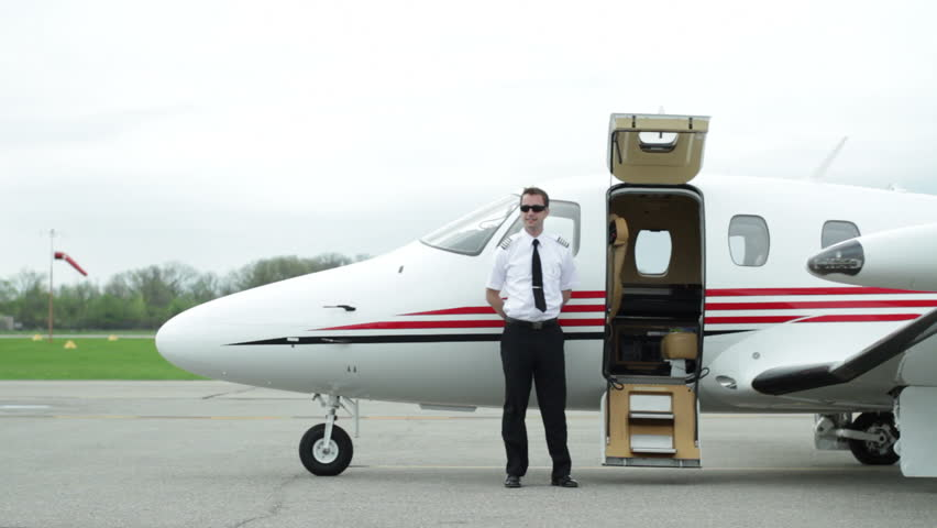 Female business executive walks up to private jet and is greeted by the pilot before she gets on. Wide shot from side.