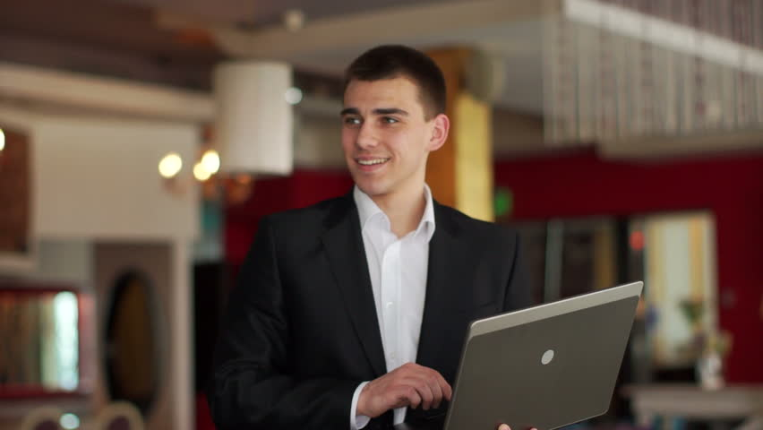 Businessman standing in cafe and typing at notebook