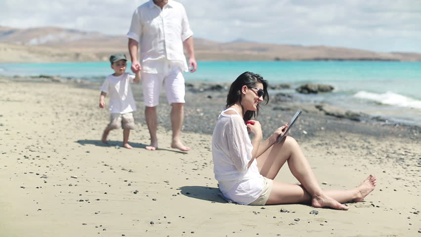 Happy family chatting with tablet computer on the beach    Shutterstock HD Video #3766217