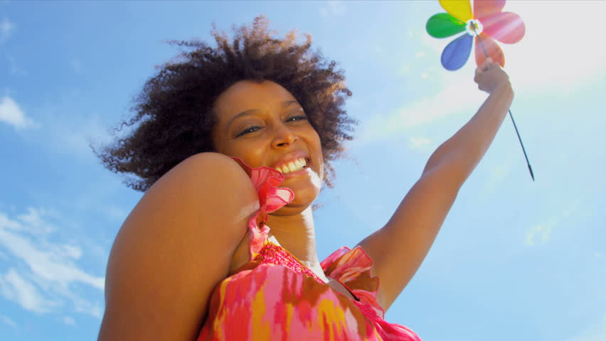 Beautiful ethnic female under blue sky watching colorful toy windmill blowing breeze shot on RED EPIC