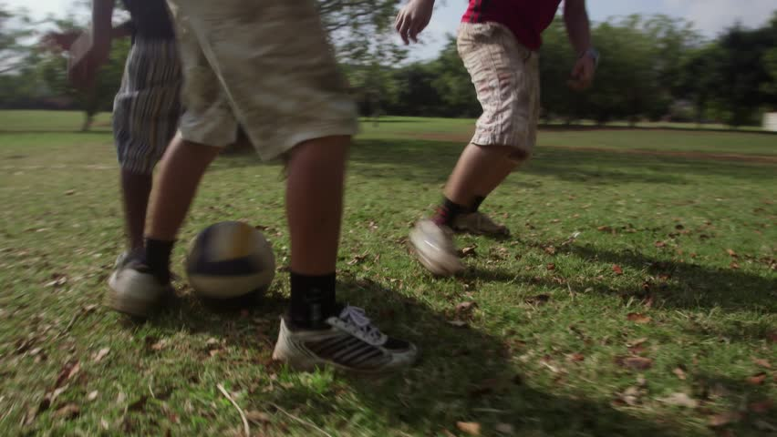 Children playing football match, group of young kids having fun with soccer game in park. Sequence, low angle view