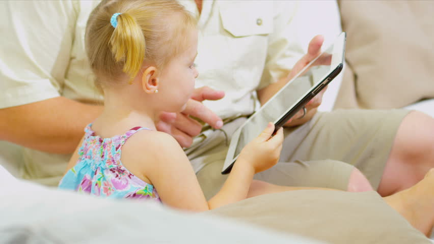 Cute blonde girls sitting with parents playing games internet wireless tablet close up shot on RED EPIC