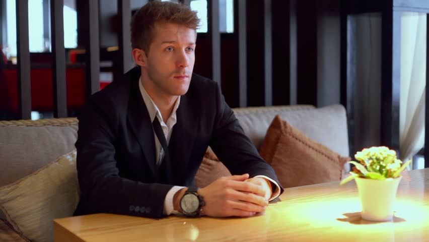 Blond man sits on sofa and looks on watch at restaurant - HD stock footage clip