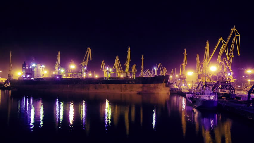 Cargo ship with cranes working on a background night.