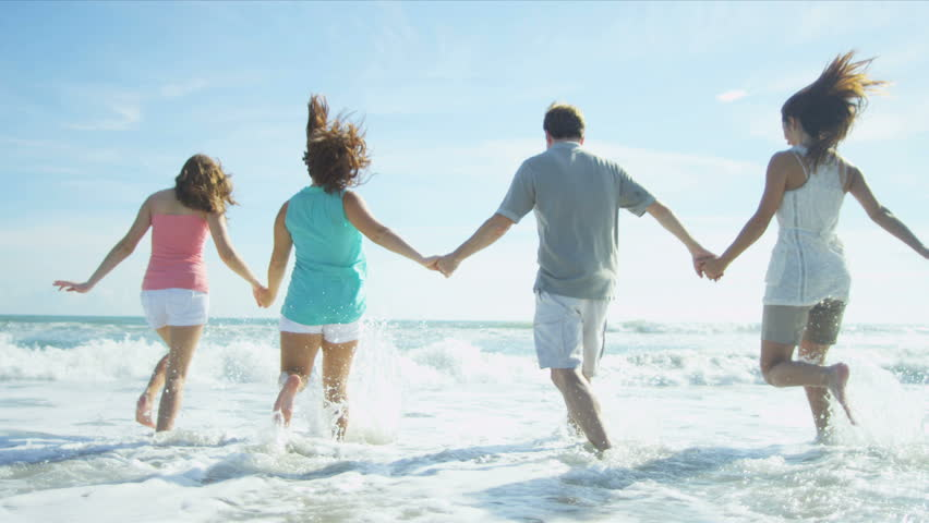 Carefree young Caucasian family happily splashing ocean shallows on beach vacation shot on RED EPIC