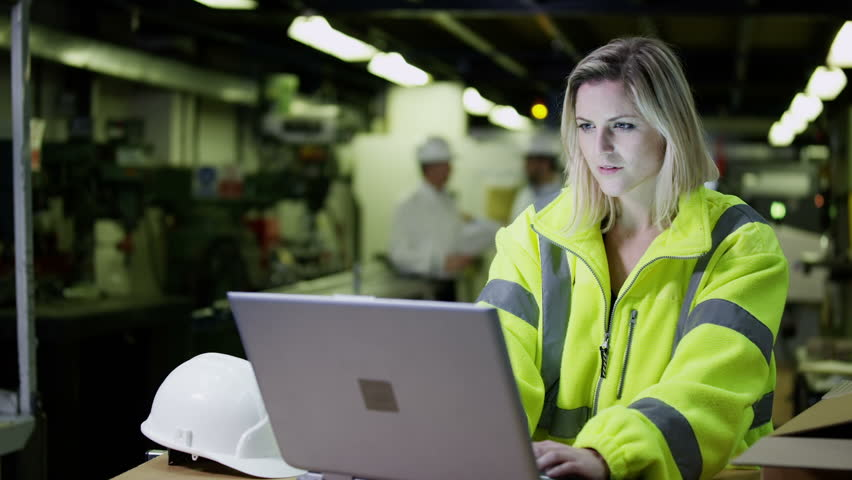 A beautiful female warehouse employee wearing high visibility clothing and a hard hat is working on a laptop computer and checking her stock. In slow motion.