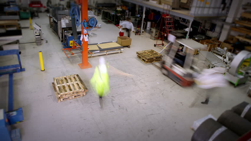 Time-lapse clip of busy workers in a warehouse or factory, wearing high visibility clothing and hard hats. They are checking stock levels and using a forklift truck to move empty wooden pallets. - HD stock video clip