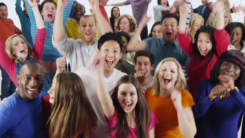 Portrait of a happy and diverse multi ethnic group of people who are standing together, in brightly colored casual clothing and having fun. They are isolated on white in a studio shot.