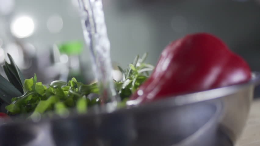 vegetarian cuisine slow motion, washing vegetables in a bowl  - HD stock footage clip