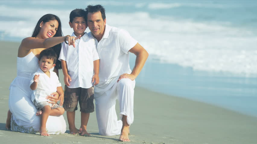 Young Latin American parents enjoying beach with little children shot on RED EPIC - HD stock footage clip