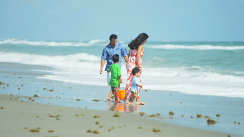 Attractive Hispanic family playing with young children on sandy beach shot on RED EPIC - HD stock footage clip