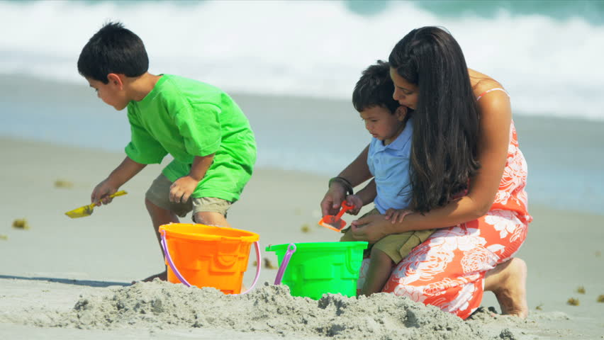 Little Latin American brothers playing together with young mother on beach shot on RED EPIC - HD stock footage clip