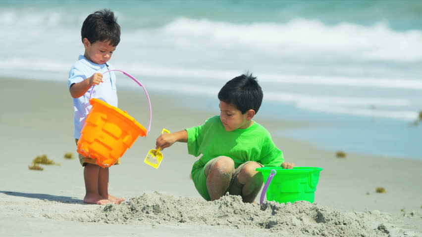 Little Hispanic brothers playing together on beach shot on RED EPIC - HD stock footage clip