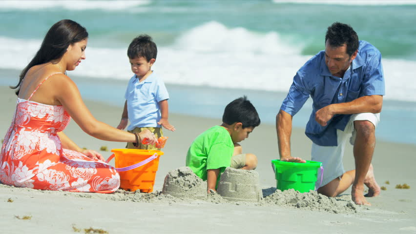Loving Hispanic family spending summer vacation playing together on sandy beach shot on RED EPIC - HD stock video clip