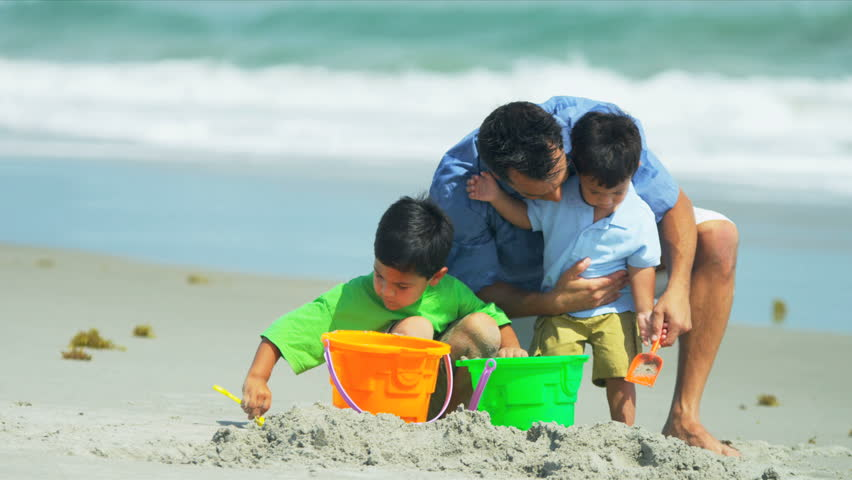 Happy Latin American boys building sand castles with young father on summer beach shot on RED EPIC - HD stock video clip