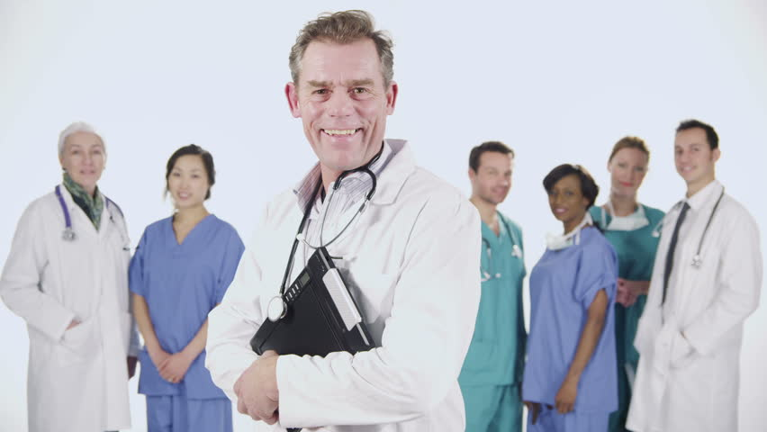 Portrait of a team of medical personnel of mixed ages and ethnicity isolated on white. They are talking amongst themselves then they all look to the camera and smile.  | Shutterstock HD Video #3823187