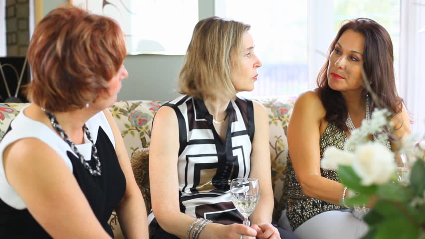 Three Mature Middle Aged Women Sat On A Sofa Talking During A House Party - HD stock video clip