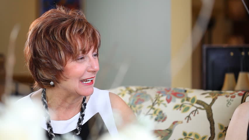 A Mature Middle Aged Baby Boomer Woman Sat On A Sofa Having A Conversation During A Party