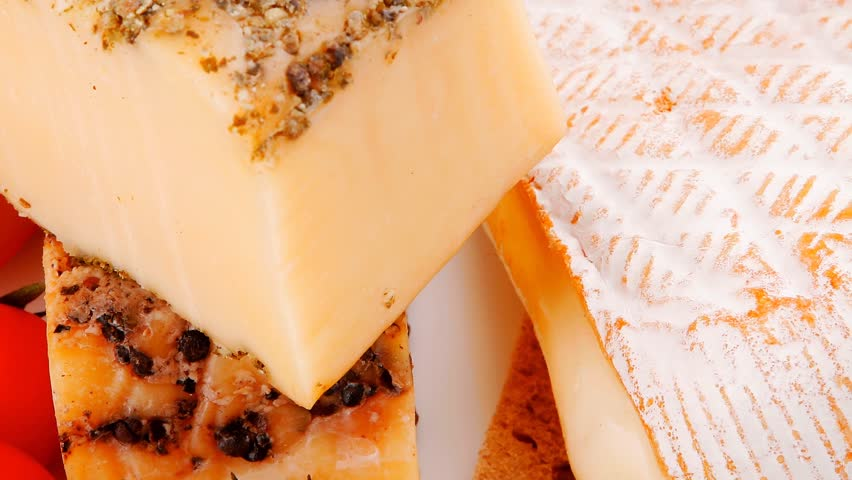 french aged cheeses on dish with bread and tomatoes - HD stock video clip