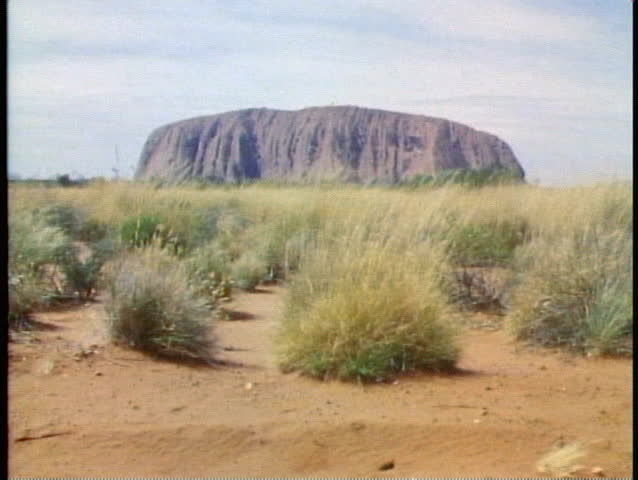 Ayres Rock, the Outback of Australia, wide shot, tumbleweeds, tilt up