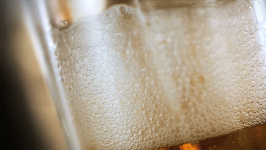 Beer is pouring into the angled glass. - HD stock video clip