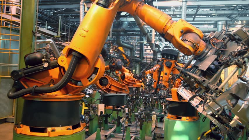 Robots weld car parts in production line at factory