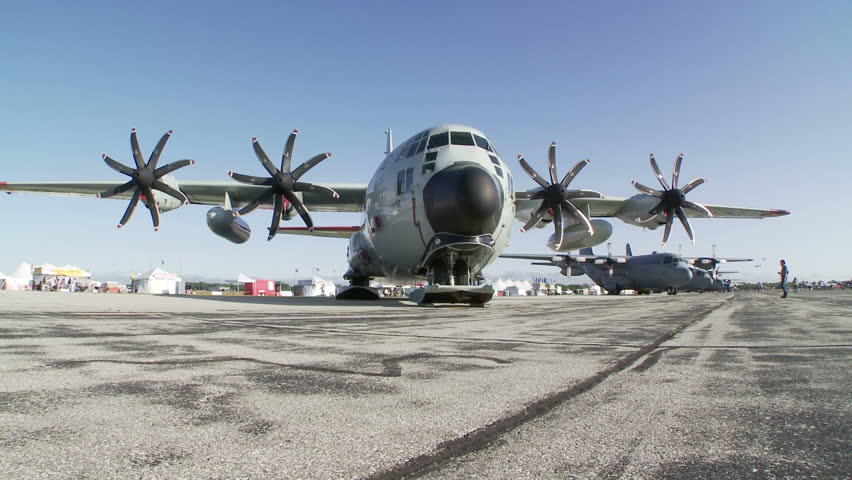 Lockheed Hercules military transport aircraft parked at an airshow.  Two clips with camera dolly.