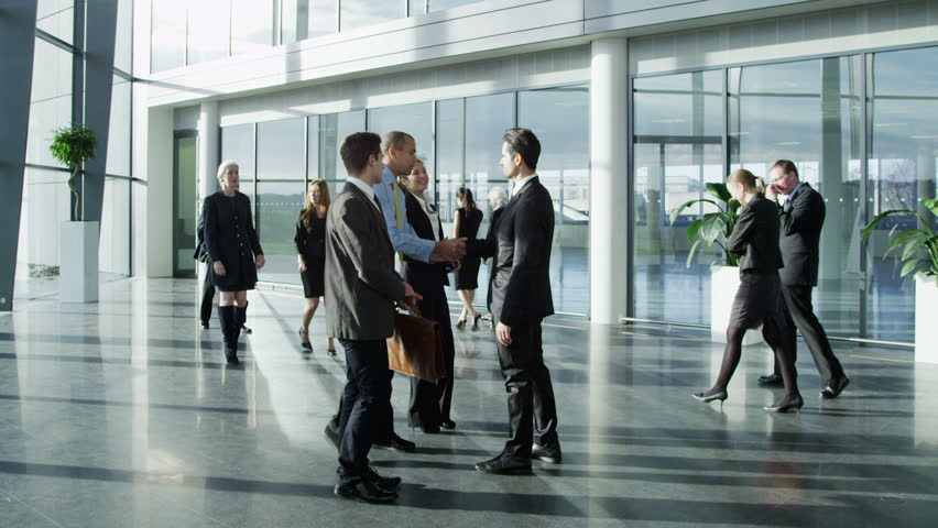 Confident and attractive young business team meet up with their client and shake hands, in a light and modern office building.