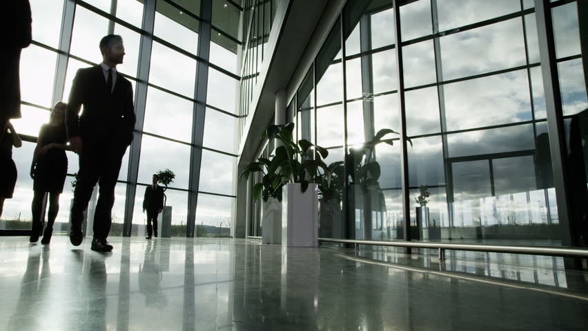 Time lapse of a large group business people moving around a large, open plan, glass fronted office building. The interior panels of glass are reflecting the clouds outside as they move across the sky.