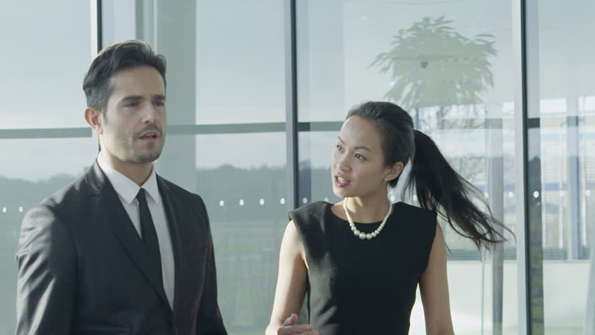 An attractive mixed ethnicity businessman and businesswoman chat together as they walk around their light and modern office building. In slow motion. - HD stock footage clip