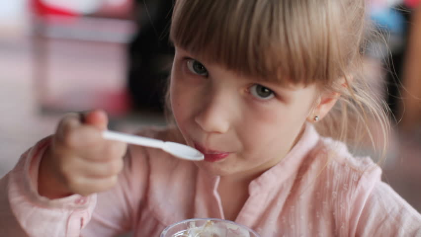 Kid sitting at cafe and eating ice-cream