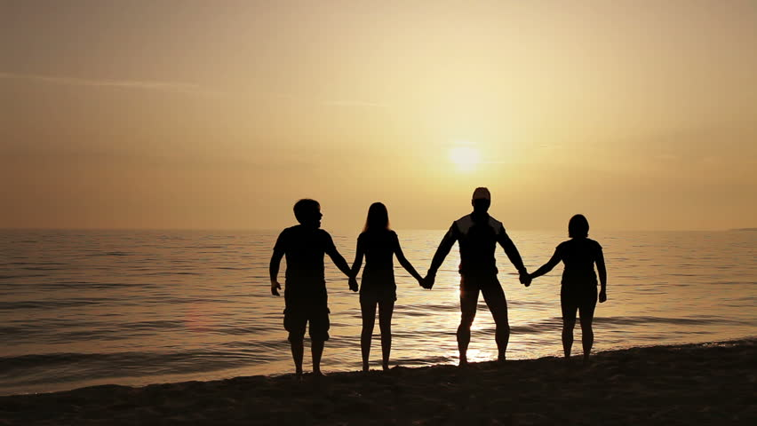 Three Children And Two Adults Jump On The Beach At Sunset ...