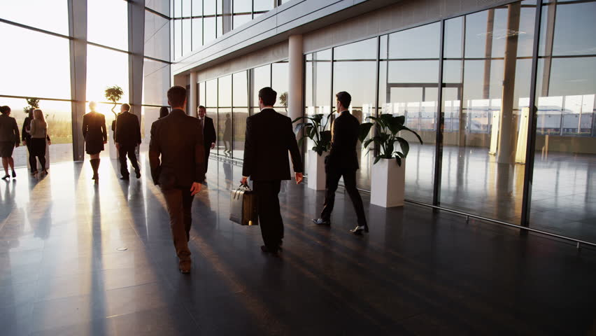 Two young businessmen who are old acquaintances, meet and shake hands in a busy modern office building at sunset.