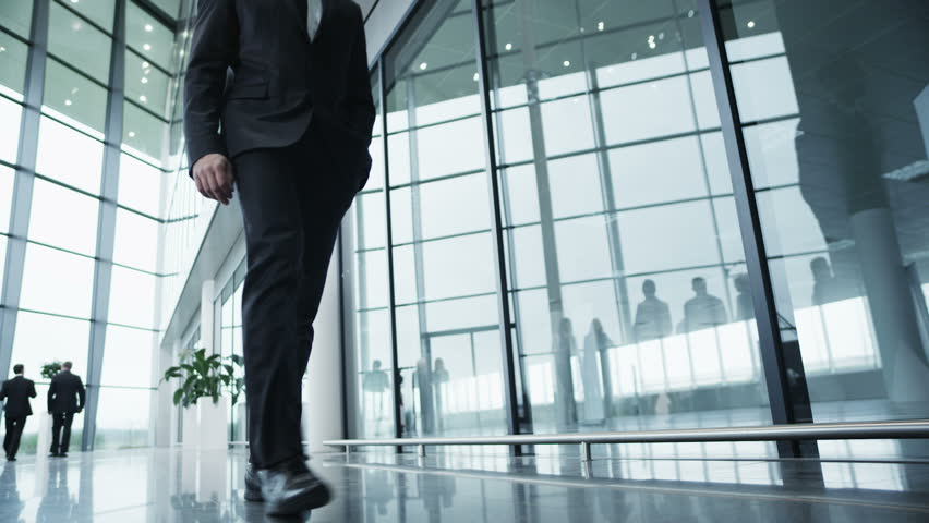 Attractive and confident businessman is walking around a light and modern open plan office building. In slow motion.