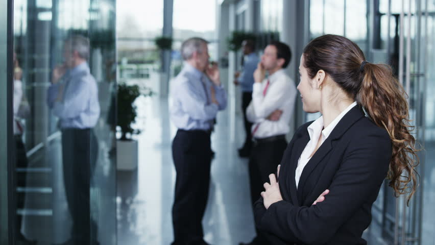 Portrait of an attractive and confident young business woman standing in a light and modern office building. The rest of her team can be seen chatting together in the background. In slow motion.