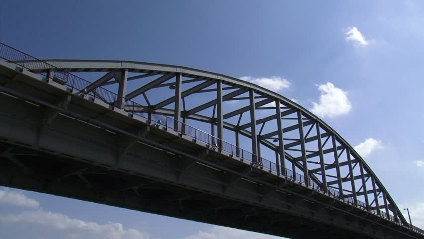 John Frost Bridge, Arnhem - low angle + tilt down rive Lower Rhine.The bridge is named after Major-General John Dutton Frost (1912-1993) and famous by the 1977 film A Bridge Too Far. - HD stock footage clip