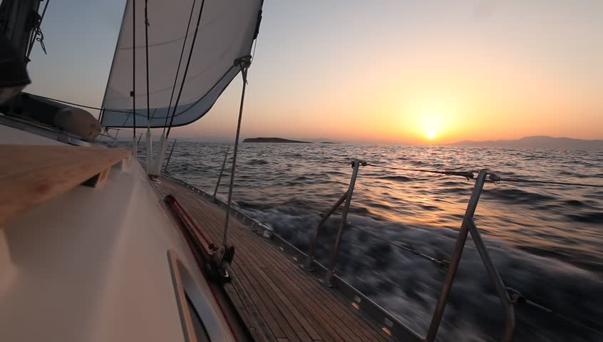 Sailing in the wind through the waves during sunset (HD) Sailing boat shot in