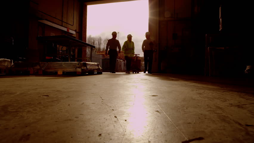 Atmospheric sepia toned clip of workers going about their business in a warehouse or storage facility. Sunlight streams into the space through the open shutter doorway. Low angle. In slow motion.