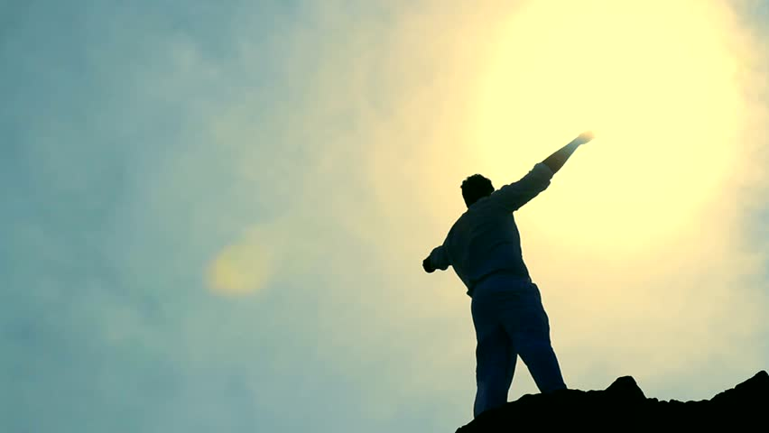 Worship Pose Colorful Silhouette of Man on Mountain Peak Raising Arms at Sun
