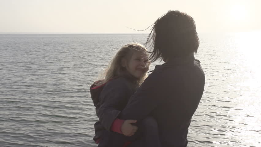 Beautiful woman holding a little girl and spinning on the beach. Slow Motion at a rate of 480 fps - HD stock footage clip