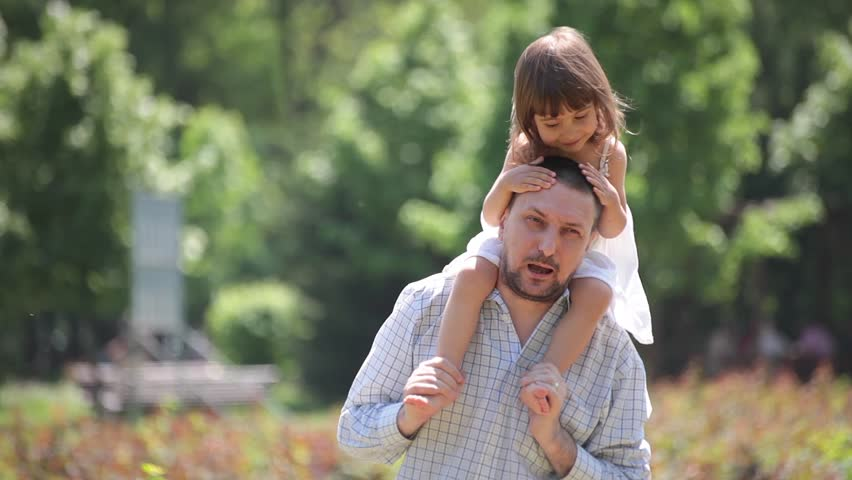 Father holds daughter on shoulders, piggybacks and plays with her.